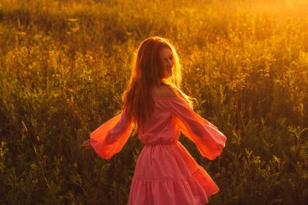 Bailando sonriente hermosa niña de vestido rosado en campo, contraluz del sol, salida del sol, los colores naranja Foto de archivo