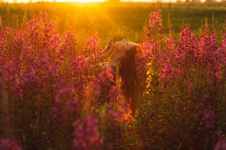 foxy girls: Beautiful girl in profile on field, sun backlight, sunrise, orange colors, hands near the neck Stock Photo