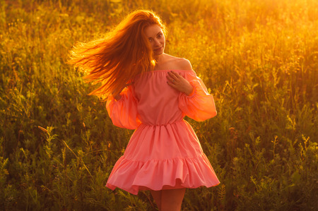 foxy girls: Dancing beautiful girl in pink dress  on field, sun backlight, sunrise, orange colors