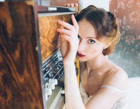 Beau portrait de jeune fille dans un style rétro sur fourrure, vieille radio, regardant vers la caméra