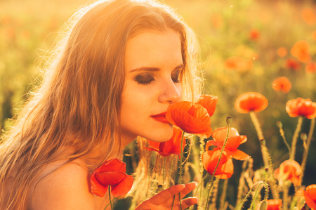 Beautiful girl  in the field sniffing poppy flower