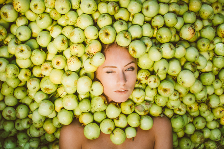 Portrait of beautiful girl that lies in the green apples, apples near the face, one closed eye