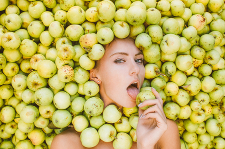 licking finger: Portrait of beautiful girl that lies in the green apples, apples near the face, licking apple