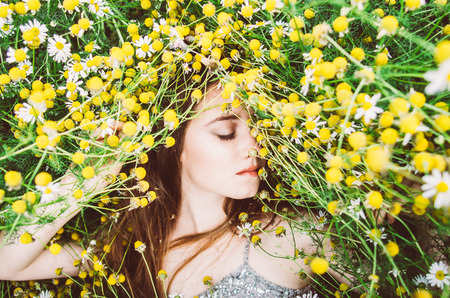 Portrait of young girl with closed eyes in chamomile field
