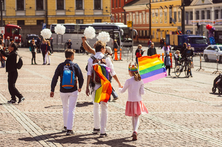Helsinki, Finland - June 30, 2018: Two women with child with rainbow flag on Helsinki pride festival on Senate square