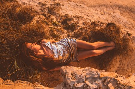 Young woman  lying on sand stone in lame dress in the evening Stock fotó