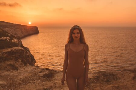 Young woman staying on mountain on shore in beige body in sunset