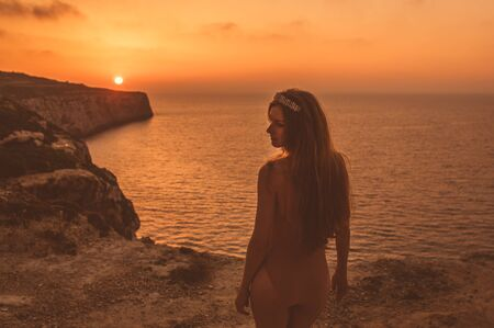 Young woman  staying on mountain on shore in beige body in sunset 写真素材