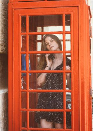 Young woman in red telephone cabin talking on the phone