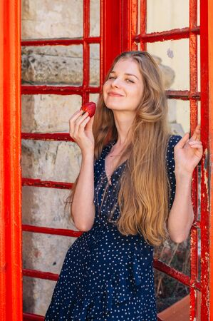 Young smiling woman with strawberry in hand in red telephone cabin 版權商用圖片
