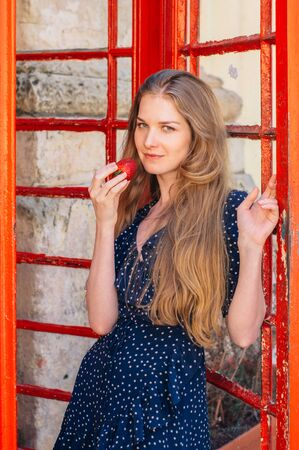 Young smiling seducing woman with strawberry in hand in red telephone cabin