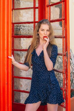 Young smiling seducing woman eating strawberry in hand in red telephone cabin