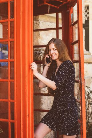 Young woman in red telephone cabin talking on the phone and smiling
