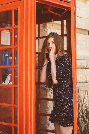 Young woman in red telephone cabin talking on the phone and surprising