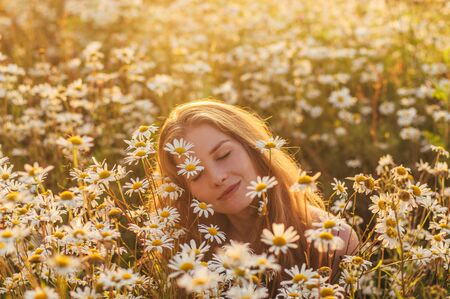 Portrait of pretty blond woman sitting in chamomile field in sunset
