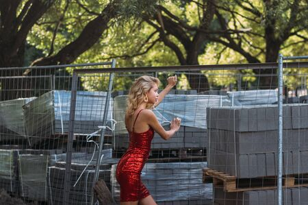 Beautiful blond girl in red short dress with sequins in park from the side  near construction site