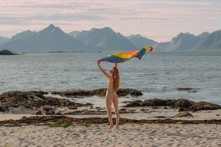 Young naked blond girl holding  LGBTQI flag above head walking in the day on the white beach near the sea, Lofoten Islands, Norway
