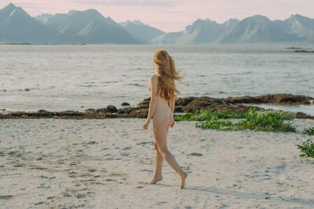 Young naked blond girl walking in the day on the white beach near the sea, Lofoten Islands, Norway