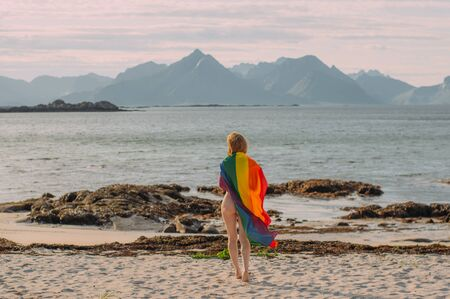 Young blond girl covered with LGBTQI flag walking in the day on the white beach near the sea, Lofoten Islands, Norway