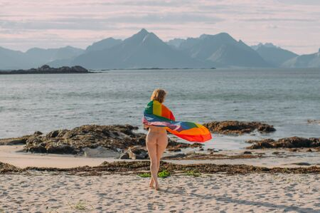 Young naked blond girl covered with LGBTQI flag walking in the day on the white beach near the sea, Lofoten Islands, Norway