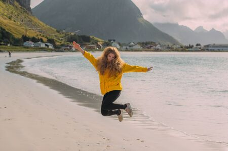 Jumping girl in yellow jacket on the white sand  beach in Ramberg on Lofoten Islands, Norway 版權商用圖片
