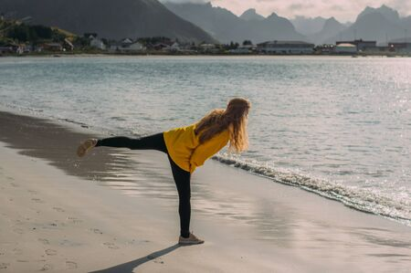 Girl in yellow jacket on the white sand  beach in Ramberg on Lofoten Islands, Norway 版權商用圖片