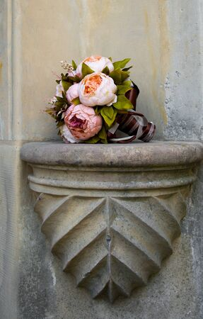 Colorful bouquet of the bride with peonies, wedding decoration with artificial flowers, old wall on background 版權商用圖片