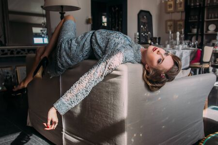 Beautiful blond girl with vintage make up and hairstyle lies on back of couch and looking up 版權商用圖片