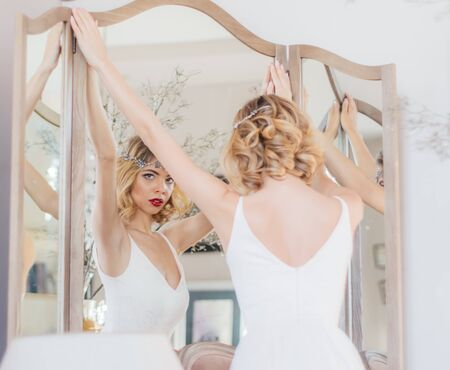 Beautiful blond girl with vintage make up and hairstyle staying near mirror with jewelry on head and looking to camera, hands on mirror