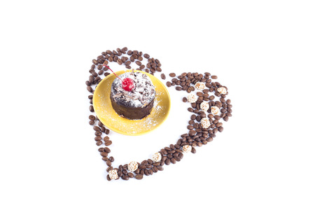 Cake on a yellow platter surrounded by grains of coffee and cookies in the shape of heart on a white background photo