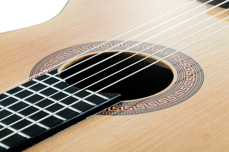 resonator: Acoustic guitar with an antique ornament and light wood closeup isolated
