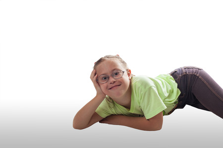 Lying horizontally girl with glasses in gray jeans on white background Stock Photo