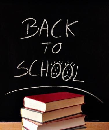the words back to school written in chalk on a blackboard, books, sad smileys