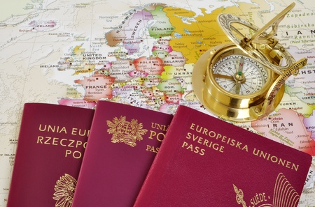 Polish, Portuguese and Swedish passport on a map with old compass photo