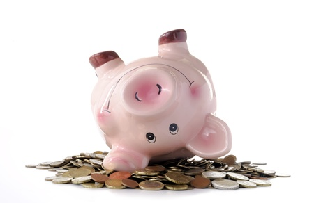 piggy banks wallowing in coins on a white background