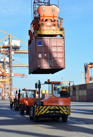 container port: crane with container and lorries