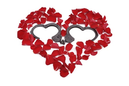 rose petals arranged in the shape of a heart and an open heart-shaped handcuffs photo