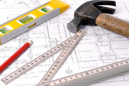 herramientas de carpinteria: Planos de la casa, viejo martillo, lápiz, nivel y medida