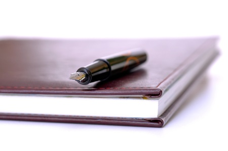 pen lying on the burgundy scrapbook, notebook Stock Photo - 13091111
