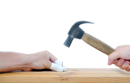 clumsy: carpenter with hammer and nail trying to avoid another injuries Stock Photo