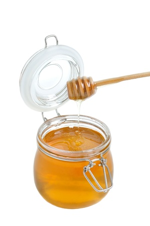 Open jar of honey and drizzler isolated photo