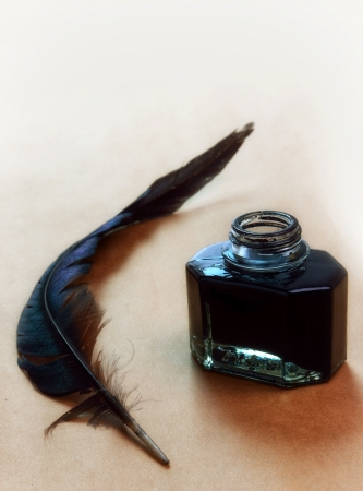 Feather and ink bottle on brown paper background photo