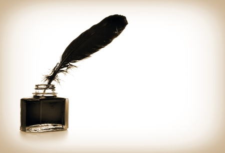 Feather and ink bottle in sepia colors photo
