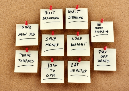Memo cards with New Years Resolutions pinned to a cork board