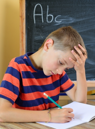 restlessness: Young boy tries to do his homework  The problem with learning Stock Photo