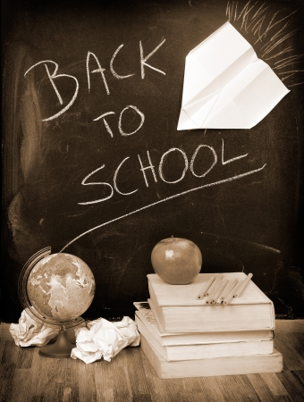 Back to School written on a blackboard with books and apple in sepia photo