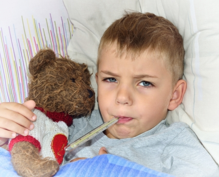 Little sick boy lying in bed with fever Stock Photo