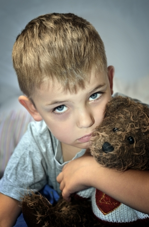 Sad little boy with a bruise under his eye clutching a teddy bear. Domestic violence.