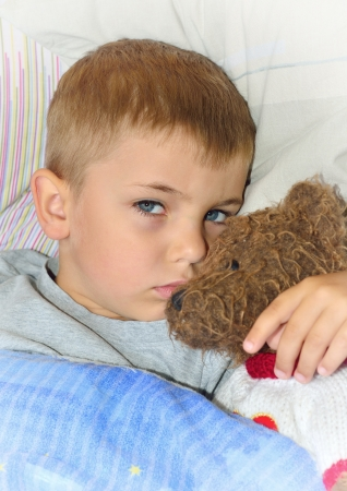 Little boy with teddy bear toy in the bed