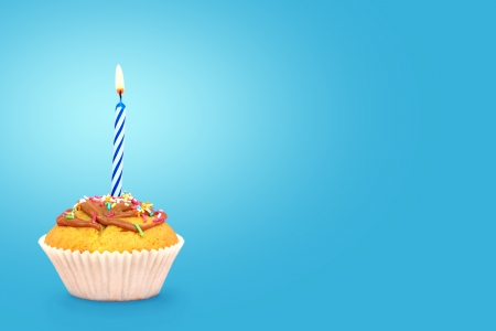 Birthday cupcake with candle on blue background Text space  photo
